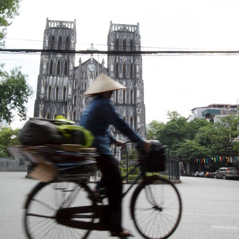 Photo of Vietnamese lady wearing conical hat cycling past the cathedral in Hanoi's French Quarter